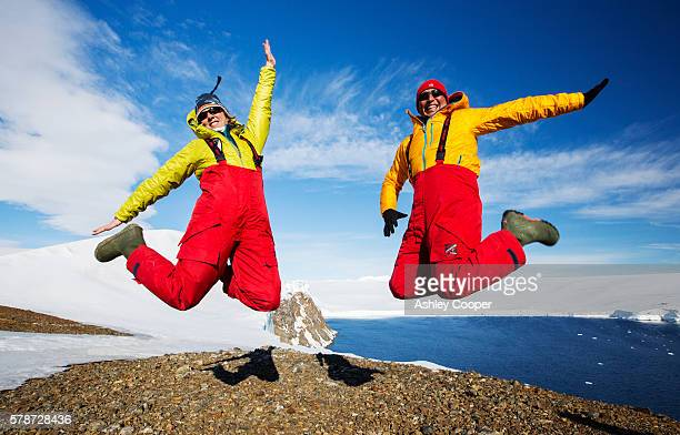 a man and woman jumping for joy from an expedition cruise on joinville island just off the antarctic peninsular. the peninsular is one of the fastest warming places on the planet. - jordanian workforce stock pictures, royalty-free photos & images