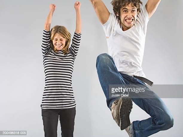 Man and woman jumping, indoors