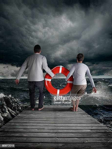 Man and woman jumping off pier with life ring