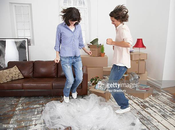 Hombre y mujer salto de envoltura de burbujas en su hogar lejos del hogar con