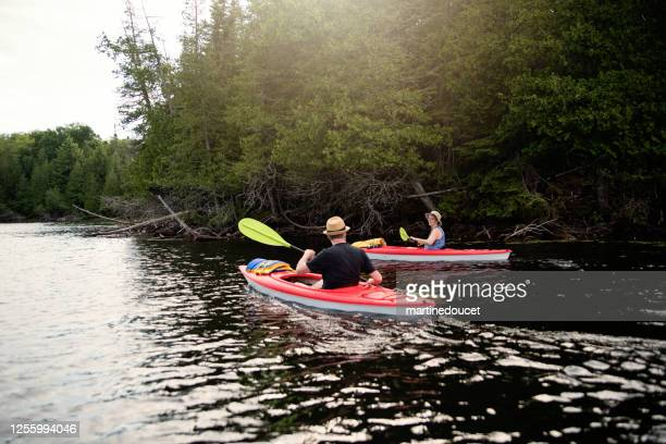 """50 + man and woman kayaking on a lake. - """"martine doucet"""" or martinedoucet stock pictures, royalty-free photos & images"""