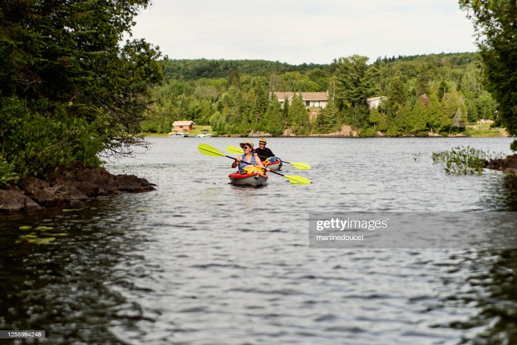 50 + man and woman kayaking on a lake. : Stock Photo