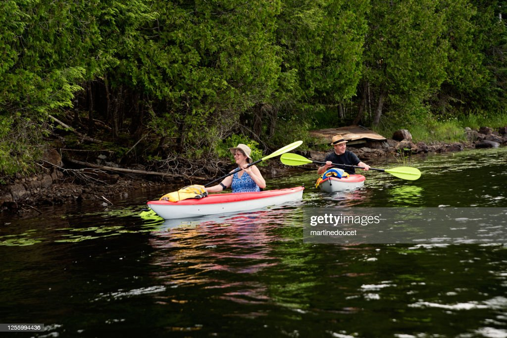 50 + man and woman kayaking on a lake. : Stock Photo