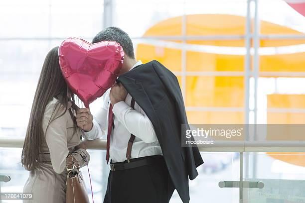 Man and woman kiss behind heart shaped balloon