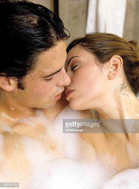 man and woman kissing in bubble bath - couple and kiss and bathroom stock photos and pictures