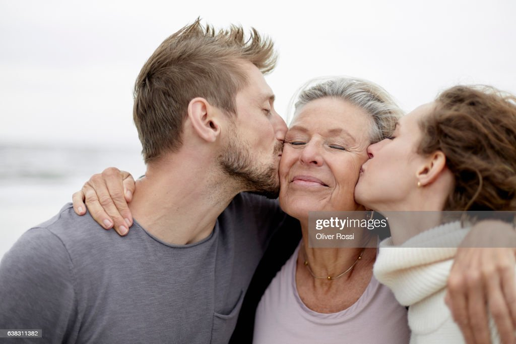 Man and woman kissing senior woman : Stock Photo