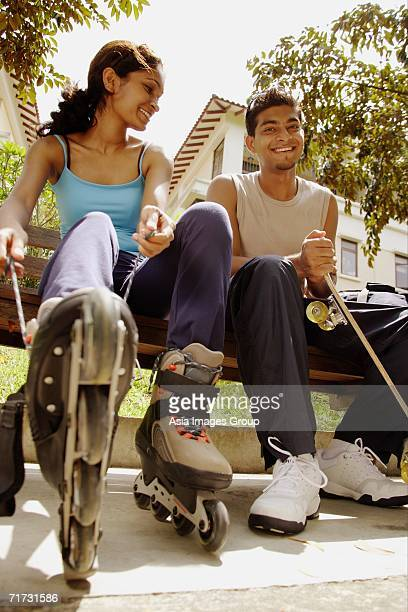 Man and woman lacing up roller blades