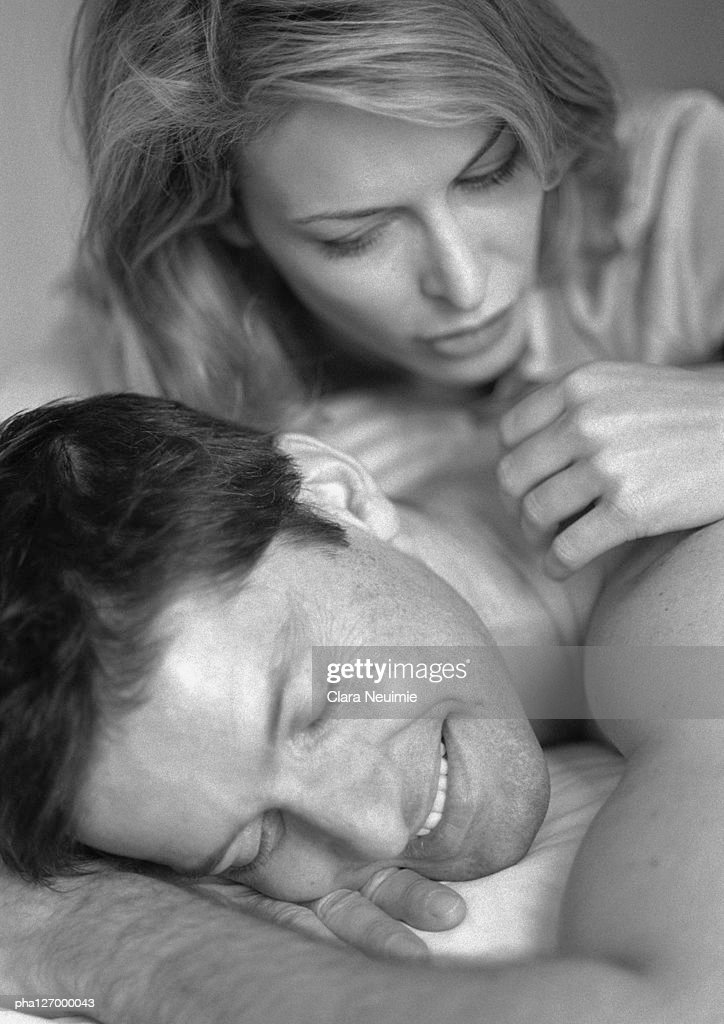 Man and woman laying on bed, close-up, b&w : Stockfoto