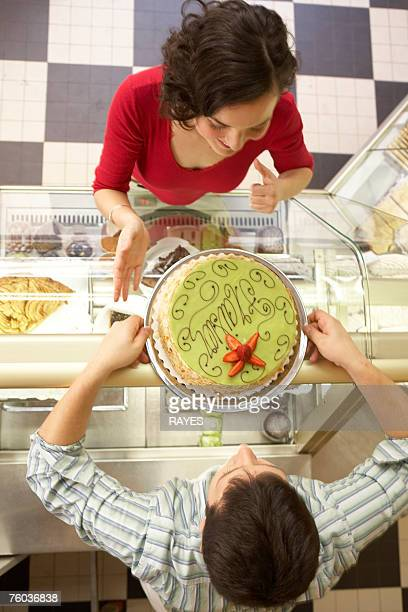 Man and woman leaning on display cabinet face to face, man holding cake, overhead view