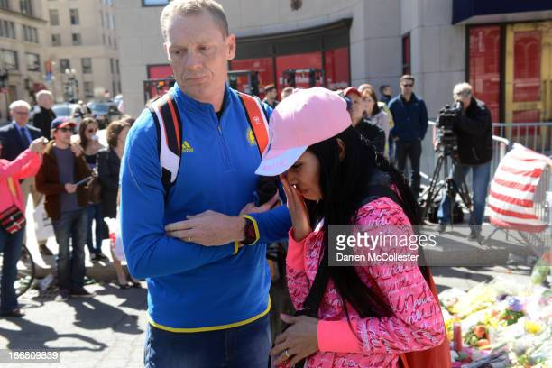 A man and woman leave after pausing at the makeshift memorial on Boylston Street to the victims of the Boston Marathon bombing April 17 2013 in...