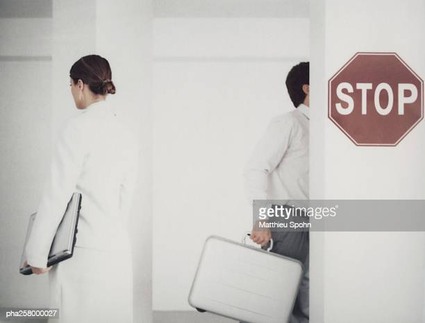 Man and woman leaving office space, rear view, stop sign on wall in front of them