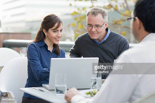Man and woman look at a computer in cafe.