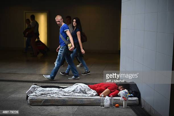A man and woman look down at a migrant sleeping on a mattress near Keleti railway station as they wait to board trains leaving for the Austrian...