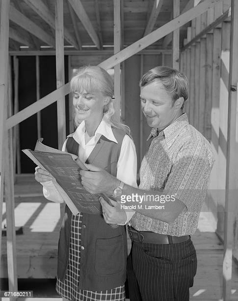 """ man and woman looking at a blueprint at construction site, smiling"" - {{relatedsearchurl(carousel.phrase)}} fotografías e imágenes de stock"