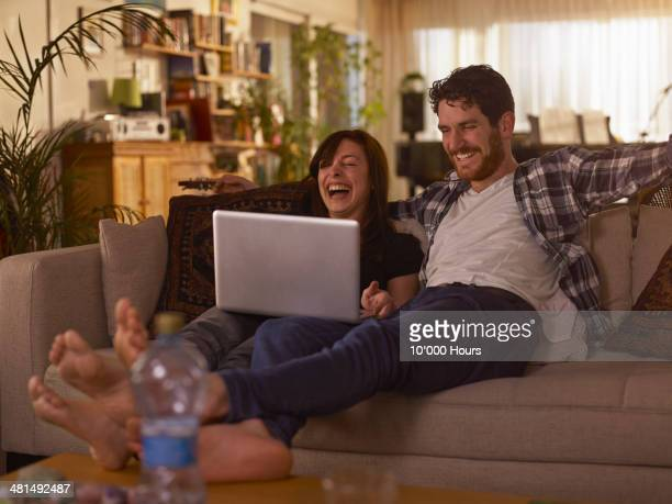 Man and woman looking at a laptop laughing