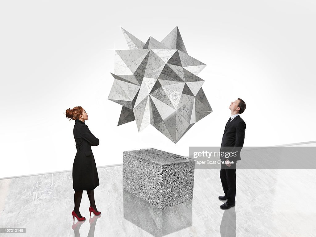 Man and woman looking at abstract art in gallery : Stock Photo