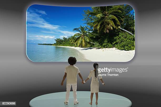 Man and woman looking at beach on monitor