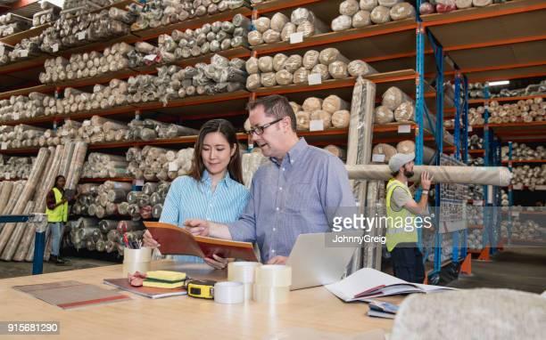 男と女のカーペット製造会社の倉庫のパンフレットを見て