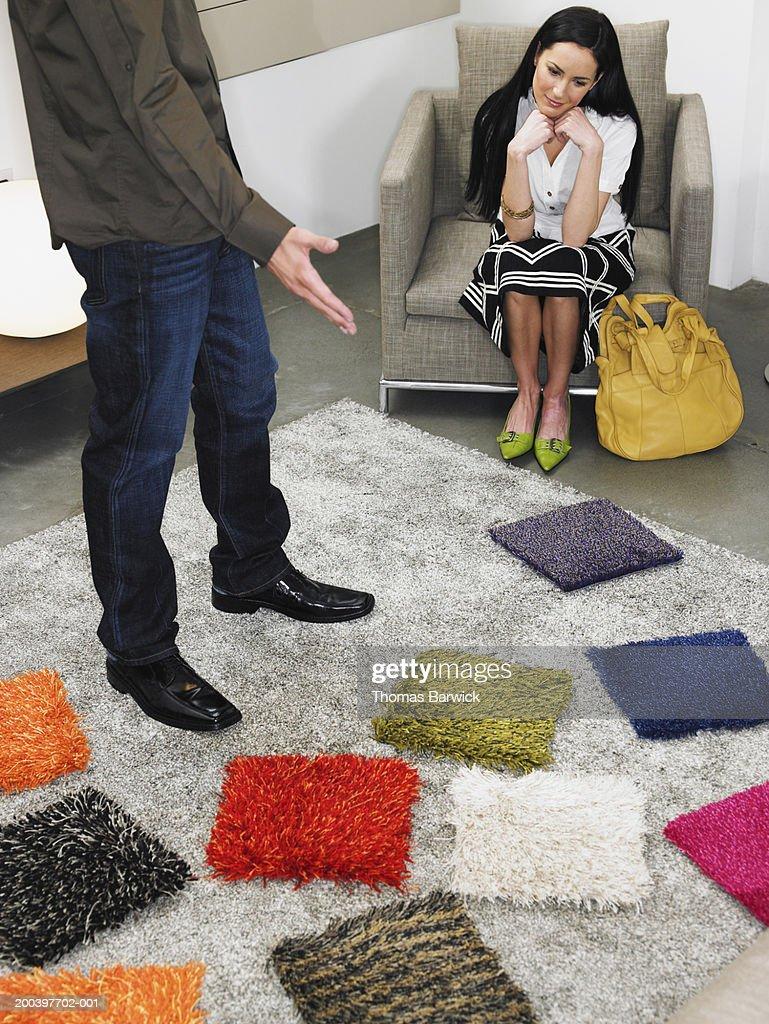 Man and woman looking at carpet samples in retail store : Foto de stock
