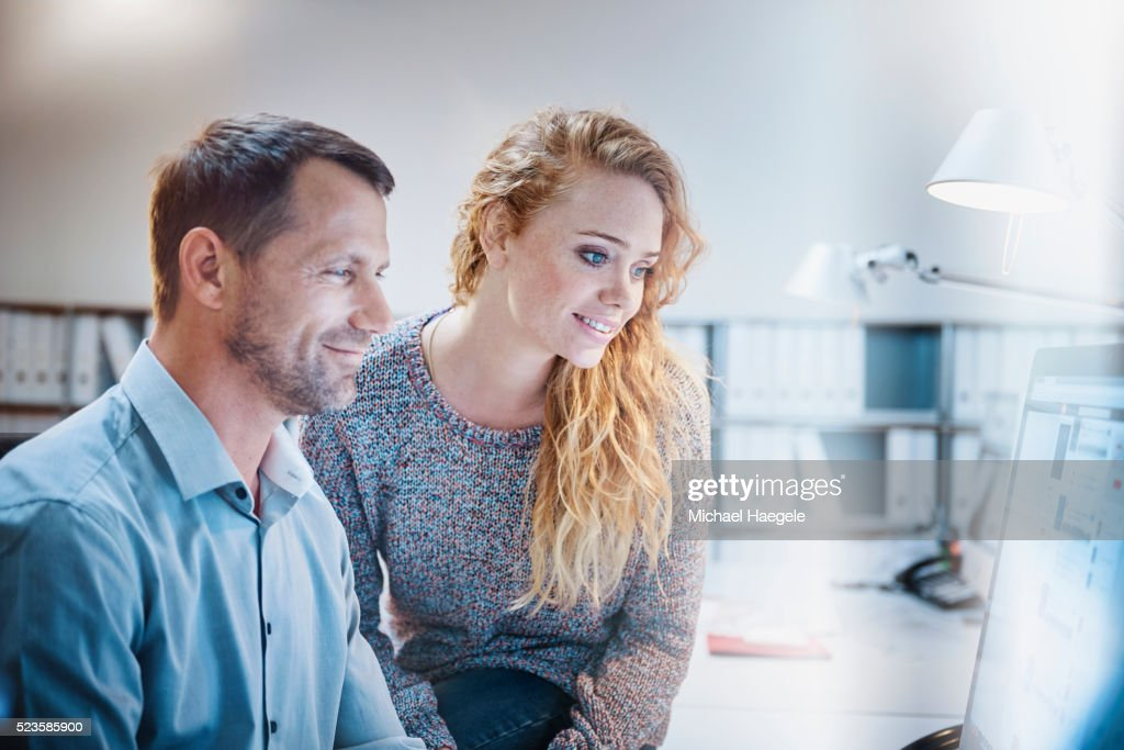 man and woman looking at computer monitor in office ストックフォト