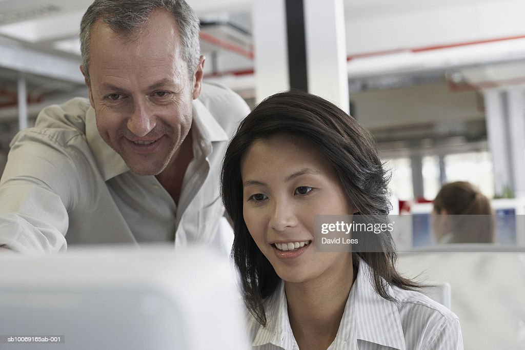 Man and woman looking at computer monitor in office : Stockfoto