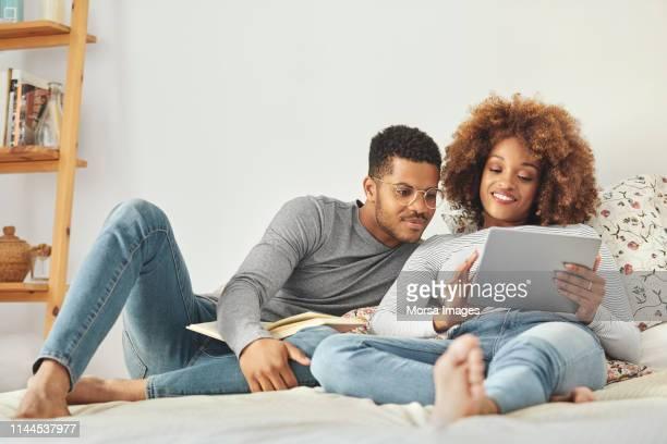 man en vrouw kijken naar digitale tablet in de slaapkamer - afro amerikaanse etniciteit stockfoto's en -beelden
