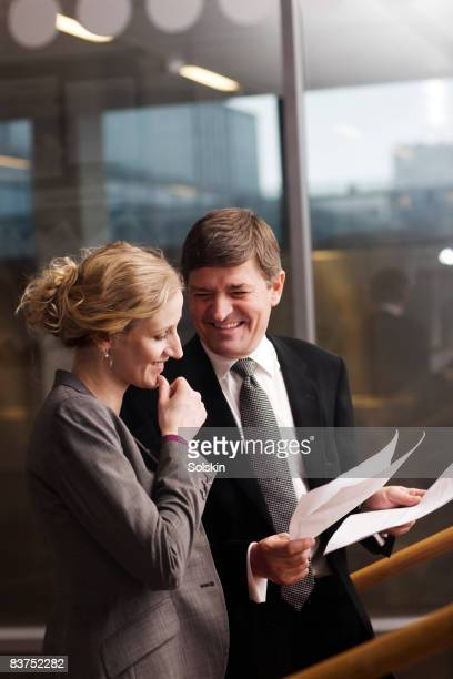 man and woman looking at documents in office
