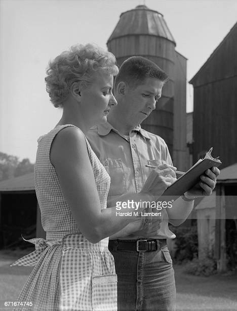 man and woman looking at documents on clipboard and discussing - {{relatedsearchurl(carousel.phrase)}} stock pictures, royalty-free photos & images
