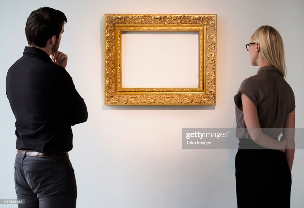 Man and woman looking at empty picture frame : Stock-Foto