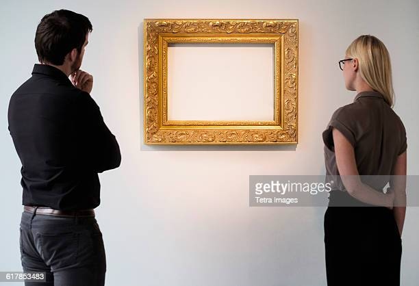 man and woman looking at empty picture frame - dreiviertelansicht stock-fotos und bilder