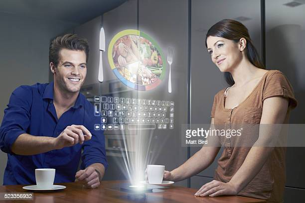 Man and woman looking at food information on futuristic device