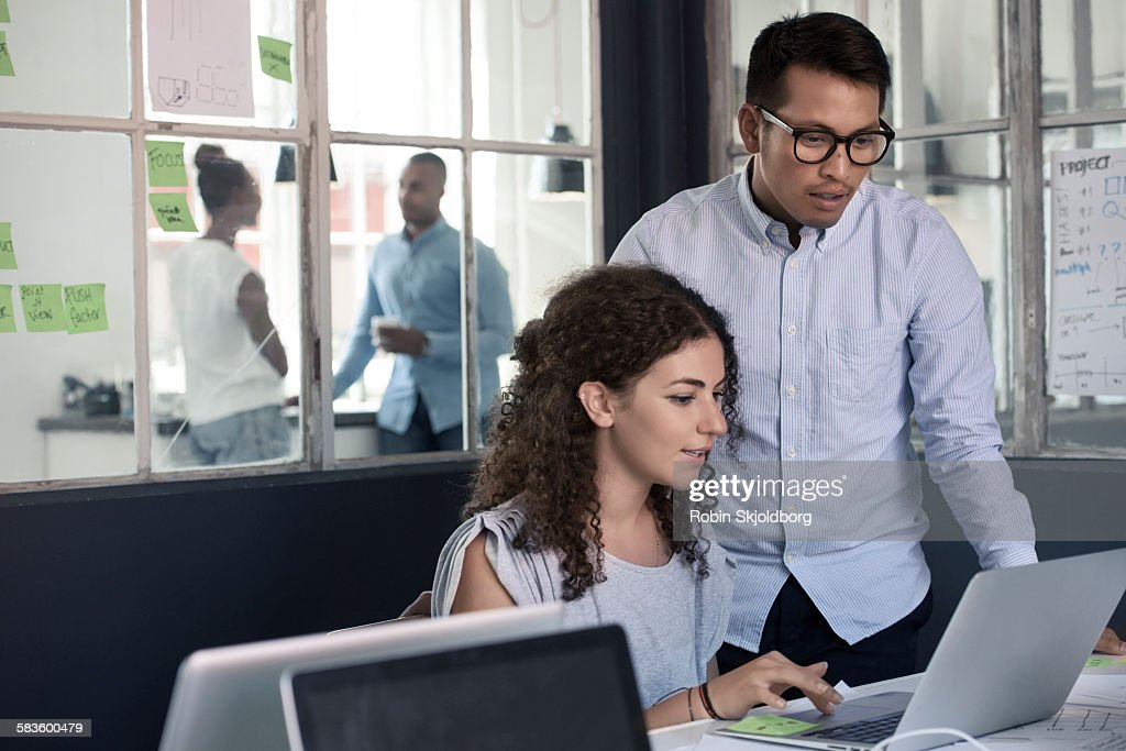 Man and Woman looking at laptop in office : Stock Photo