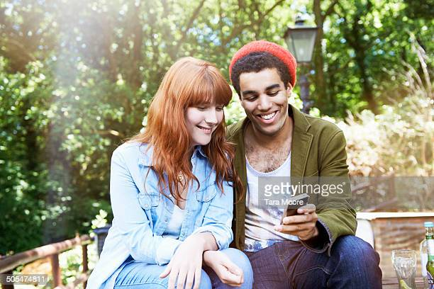 man and woman looking at mobile in park