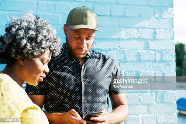 man and woman looking at smart phone - building exterior stock pictures, royalty-free photos & images