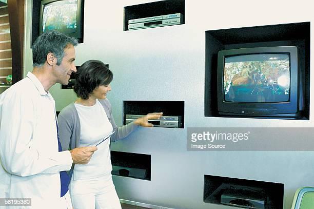 Man and woman looking at televisions