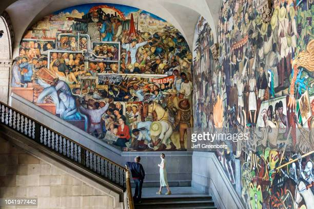 A man and woman looking at the mural on the central stairway at the National Presidential Palace
