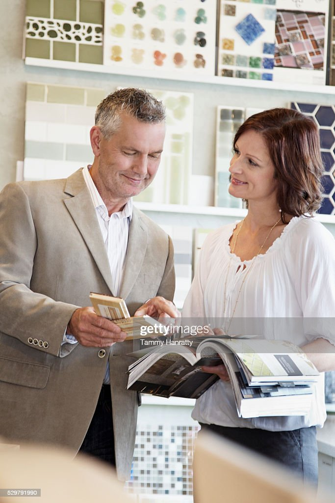 Man and woman looking at tile samples : Stock Photo