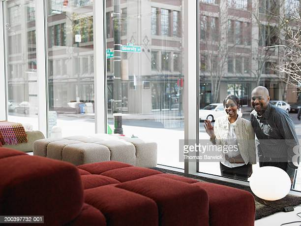 Man and woman looking at window display in retail furniture store