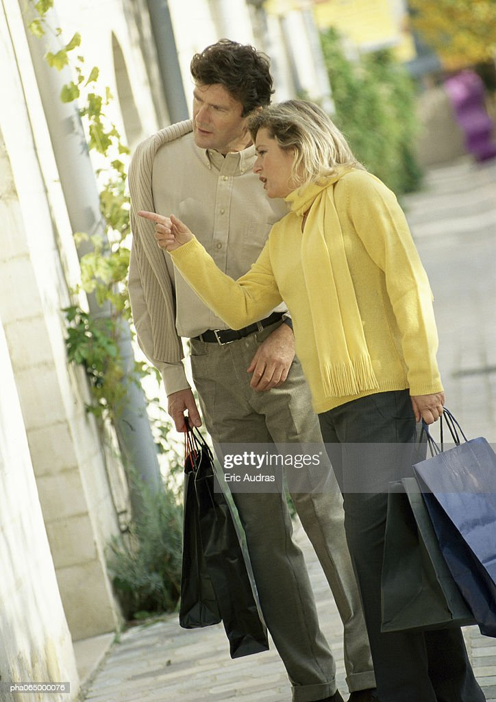 Man and woman looking in store window, side view, full length : Stockfoto