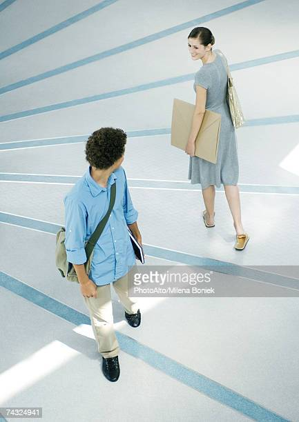 man and woman looking over shoulders at each other in passing, full length, high angle view - moving past stock photos and pictures