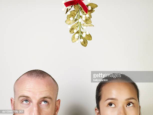 man and woman looking up at mistletoe, high section - gui photos et images de collection