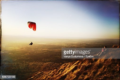 Man And Woman Looking While Person Paragliding Over Mountain Against Sky