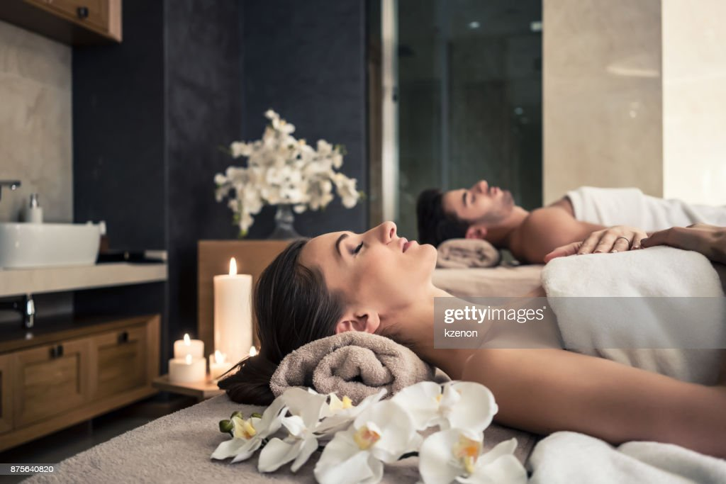 Man and woman lying down on massage beds at Asian wellness center : Stock Photo