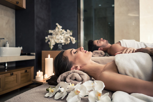 Man and woman lying down on massage beds at Asian wellness center 875640820
