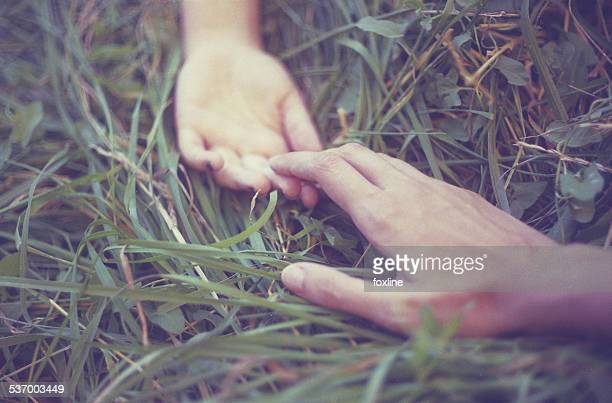 Man and woman lying in grass holding hands