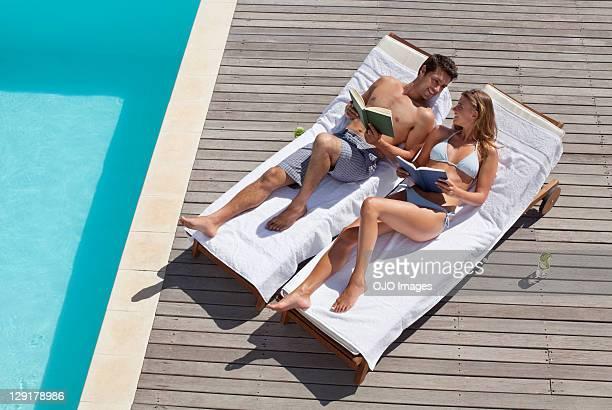 homme et femme allongée sur une chaise longue près de la piscine - transat photos et images de collection