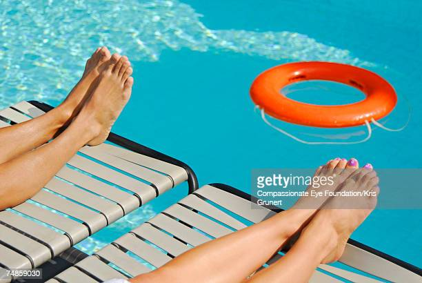 Man and woman lying on lounge chair at swimming pool, low section