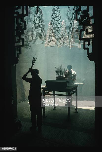 A man and woman make offerings of joss sticks at the Thien Hau Pagoda a temple built in the early 1800s to honor the Goddess of the Sea