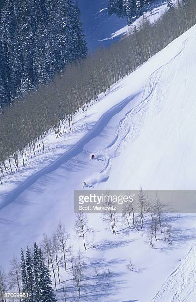 man and woman making ski tracks in the powder snow in utah. - park city utah stock pictures, royalty-free photos & images