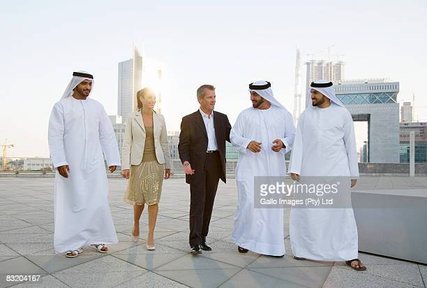 Man and woman meeting with men in traditional Middle Eastern attire, Dubai cityscape in background, UAE